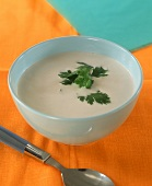 Coconut milk and banana cream with coriander leaves in bowl