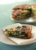 Piece of spinach and olive quiche with pine nuts