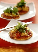 Mini-pizza with artichokes, tomatoes and rocket