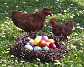 Easter eggs in nest and chicken figures in a meadow