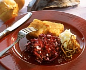 Breaded fish slices with red cabbage and mashed potato