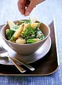 Warm potato salad with spinach and lemon zest
