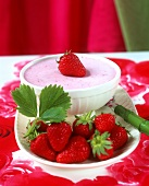 A bowl of strawberry cream and fresh strawberries