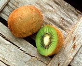 Kiwi fruits, whole and cut open, leaf in background