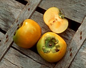Two whole and one half sharon fruit (Sharon persimmon)
