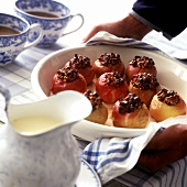 Hände servieren Bratäpfel mit Vanillesauce