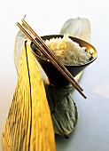 Boiled rice in a wooden bowl; chopsticks