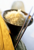Chopsticks on wooden bowl of boiled rice