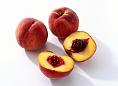 Two whole and one halved peach