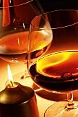 Brandy in Cognacschwenkern neben Kerze auf dem Tisch
