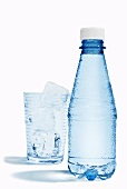 A bottle of mineral water and a glass with ice cubes