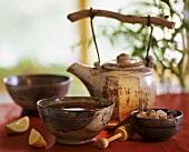 Asian teapot, two bowls of tea and sugar crystals