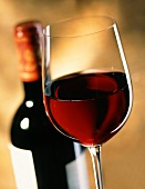 Glass of red wine in front of bottle