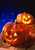Two pumpkin lanterns for Halloween on straw