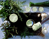 Several bowls of herb butter and various kinds of herbs