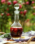 Liqueur with fresh rose petals in a carafe