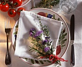 Plate with napkin and bunch of herbs