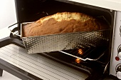 Taking loaf cake out of the oven