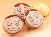 Amerikaner (soft, sponge cake-like shortbreads) iced with faces