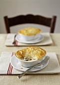 Red snapper in white wine sauce under puff pastry topping