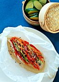 Chicken breast, strips of vegetables & sesame on baking paper