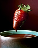 Strawberry being dipped in chocolate fondue