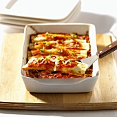 Enchiladas with beef filling in baking dish