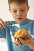 Boy brushing muffin with glacé icing