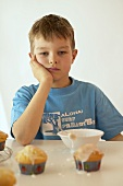 Boy with glacé icing and iced muffins