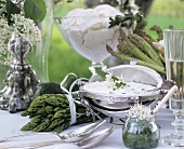 Herb quark in silver bowl and green asparagus