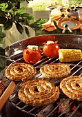 Sausage coils, tomatoes and sweetcorn on a barbecue