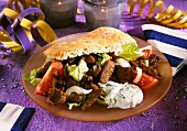 Pan gyros with salad and tzatziki in flatbread on plate