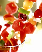 Fresh fruit kebabs sticking out of a glass