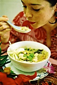 Woman eating Asian chicken & vegetable soup (surreal photo)