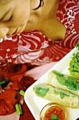 Europäerin isst vietnamesische Frühlingsrollen (verfremdet)