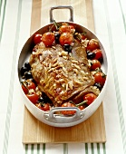 Shoulder of lamb with tomatoes, olives, pine nuts in meat dish