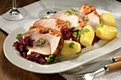 Stuffed rolled pork joint with red cabbage and boiled potatoes