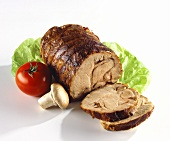 Rolled roast, slices carved, with salad decoration