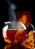 Steaming red wine punch with pieces of fruit in glass teapot