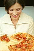 Young woman in front of pizza with a piece cut (grainy effect)