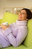 Young woman on sofa with tea or coffee cup (grainy effect)