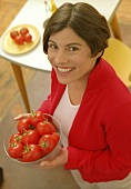Woman holding dish of tomatoes (grainy effect)
