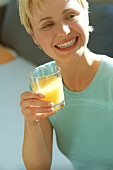 Sporty young woman with glass of orange juice (grainy effect)