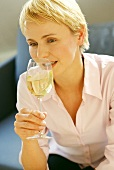 Young blond woman with glass of white wine (grainy effect)