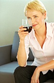 Blond woman holding glass of red wine (grainy effect)