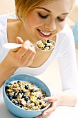 Young woman eating muesli with blueberries