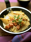 Potato and pumpkin curry with onions in a frying pan