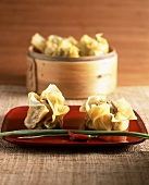 Dim sum (Chinese pastry purses) on platter and in steamer