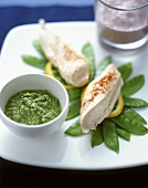 Steamed chicken breast on mangetout peas with herb dip