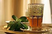 Peppermint tea in Middle Eastern glass & fresh mint leaves